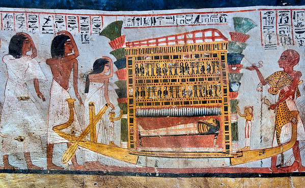 """[EGYPT 29375] 'Funerary barque in Roy's tomb at Luxor.'  A mural detail in the tomb of Roy shows his mummy being transported in a shrine on a sled which has the form of a boat. A large bouquet of flowers is attached to either side of the shrine which is decorated with Djed pillars (signifying endurance) and Tyet knots (signifying life). The deceased is protected by statues with raised hands of Isis en Nephthys, the goddesses who protected their dead brother Osiris according to Egyptian mythology. The sled is followed by relatives and friends who make gestures of mourning. In front of the sled a Sem priest in a leopard skin performs a fumigation with incense and a libation with water. Roy was an 18th dynasty royal scribe during the reign of Horemheb. His tomb (TT 255) can be found in the Necropolis of Dra Abu el-Naga on the Westbank at Luxor. It is one of the socalled """"Tombs of the Nobles"""". Photo Mick Palarczyk and Paul Smit."""