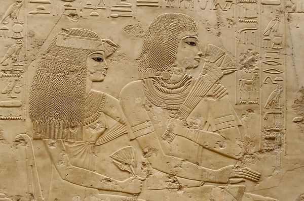 """[EGYPT 29333] 'Guests at funeral banquet in Ramose's tomb at Luxor.'  Guests at the funeral banquet of Ramose adorn the wall left of the entrance to his tomb. Depicted are Neby and Apuya, the parents of Ramose. The scene is carved with very fine detail into limestone and left uncoloured except for the eyes of the figures. Ramose was an 18th dynasty 'Governor of the Town' (of Thebes) and Vizier during the transition of the reigns of Amenhotep III and Echnaton. His tomb (TT 55) is located in the Sheikh Abd el Qurnah Necropolis on the Westbank at Luxor and is one of the socalled """"Tombs of the Nobles"""". It is uncertain whether he was ever buried in this tomb or that he followed Echnaton to his new capital near Amarna and was buried there. Photo Mick Palarczyk and Paul Smit."""