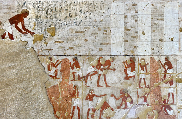 "[EGYPT 29361] 'Building scene in Rekhmire's tomb at Luxor.'  	A mural in the tomb of Rekhmire shows several scenes representing the types of labor carried out by craftsmen who worked for the Amon Temple in Karnak. In the upper register we see on the right three white pillars of a hypostyle hall under construction. The space between the pillars is filled up with mud bricks, making it possible to position on them architraves or ceiling slabs, which are transported upward over the mud brick ramp on the left. In the lower register sculptors working on scaffolds carve two colossal royal statues from red granite, a sitting figure on the left and a standing one on the right. In between a limestone sphinx is smoothed and polished. Rekhmire was an 18th dynasty vizier (viceroy) of Southern Egypt, mayor of Thebes and steward of the Amon Temple at Karnak during the reigns of Thutmosis III and Amenhotep II. His tomb (TT 100) is located in the Sheikh Abd el Qurnah Necropolis on the Westbank at Luxor and is one of the socalled ""Tombs of the Nobles"". Photo Mick Palarczyk and Paul Smit."