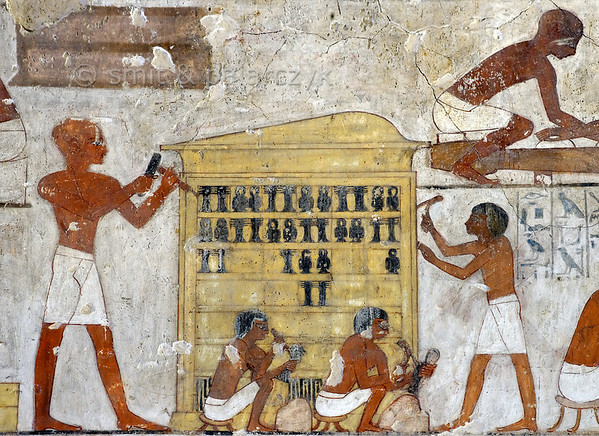 "[EGYPT 29358] 'Decorating a shrine in Rekhmire's tomb at Luxor.'  	A mural in the tomb of Rekhmire shows several scenes representing the types of labor carried out by craftsmen who worked for the Amon Temple in Karnak. Here we see four men putting the finishing touch on a shrine elaborately crafted of fine woods. The man on the left is working with a chisel and hammer while the one on the right uses an adze. The two craftsmen in the middle are making the black decorations that will be inserted into the surface of the shrine: the Djed pillar (endurance) and the Tyet knot (life). A decoration pattern that can be found, for instance, on the outer shrine of Tutankhamun. Rekhmire was an 18th dynasty vizier (viceroy) of Southern Egypt, mayor of Thebes and steward of the Amon Temple at Karnak during the reigns of Thutmosis III and Amenhotep II. His tomb (TT 100) is located in the Sheikh Abd el Qurnah Necropolis on the Westbank at Luxor and is one of the socalled ""Tombs of the Nobles"". Photo Mick Palarczyk and Paul Smit."