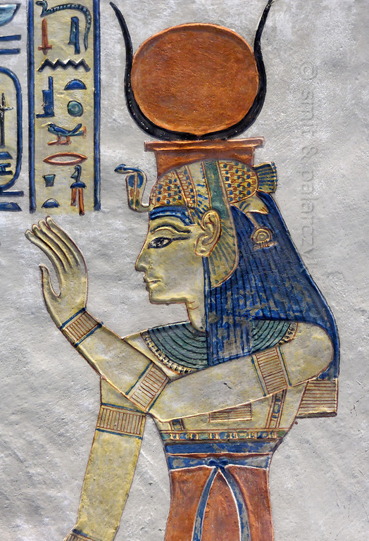 [EGYPT 29411] 'Isis in the tomb of Amenherkhepshef.'  	This coloured relief in the tomb of Amenherkhepshef portrays the goddess Isis, wearing a blue wig topped by a vulture headdress and the sun disc between cows horns. Amenherkhepshef was a royal scribe, commander of the cavalry and son of Ramses III. His tomb (QV 55) can be found in the Valley of the Queens on the Westbank at Luxor. Photo Mick Palarczyk and Paul Smit.