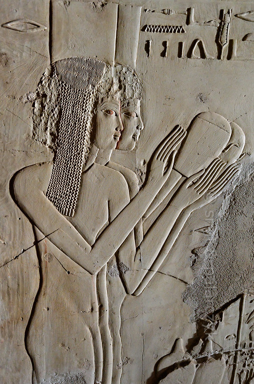 "[EGYPT 29397] 'Princesses in Kheruef's tomb at Luxor.'  	This relief detail in the tomb of Kheruef shows two of the eight 'princesses' that perform libations from spouted vessels on the occasion of the First Jubilee (heb sed) festival of Amenhotep III (in year 30 of his reign). The girls are probably daughters of foreign rulers raised at the court of the pharaoh. They wear the diaphanous flowing garments of their time. Kheruef was steward of Queen Tiy, the wife of Amenhotep III, and played an important role during festivals. His (unfinished) tomb (TT 192) can be found in the Asasif Necropolis on the Westbank at Luxor. It is one of the socalled ""Tombs of the Nobles"". Photo Mick Palarczyk and Paul Smit."
