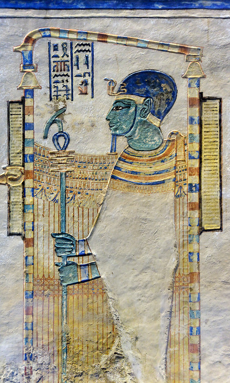 [EGYPT 29408] 'Ptah in the tomb of Amenherkhepshef.'  	Standing in a shrine and wearing his typical blue cap, this coloured relief in the tomb of Amenherkhepshef portrays the god Ptah. According to the cosmogony of Memphis, Ptah was the god who conceived the world by the power of his thoughts and words, not unlike the judeo-christian god.  Amenherkhepshef was a royal scribe, commander of the cavalry and son of Ramses III. His tomb (QV 55) can be found in the Valley of the Queens on the Westbank at Luxor. Photo Mick Palarczyk and Paul Smit.