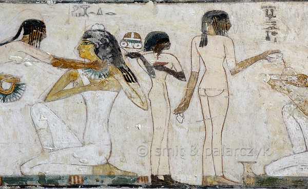 "[EGYPT 29354] 'Servant girls in Rekhmire's tomb at Luxor.'  	In Rekhmire's tomb a large painting in several registers shows his funeral banquet. On the left we see a detail with a servant girl offering a necklace to a seated female guest. On the right is the famous scene of a servant girl who is shown with her back to us in a three-quarter view that is unique in Egyptian art. Rekhmire was an 18th dynasty vizier (viceroy) of Southern Egypt, mayor of Thebes and steward of the Amon Temple at Karnak during the reigns of Thutmosis III and Amenhotep II. His tomb (TT 100) is located in the Sheikh Abd el Qurnah Necropolis on the Westbank at Luxor and is one of the socalled ""Tombs of the Nobles"". Photo Mick Palarczyk and Paul Smit."