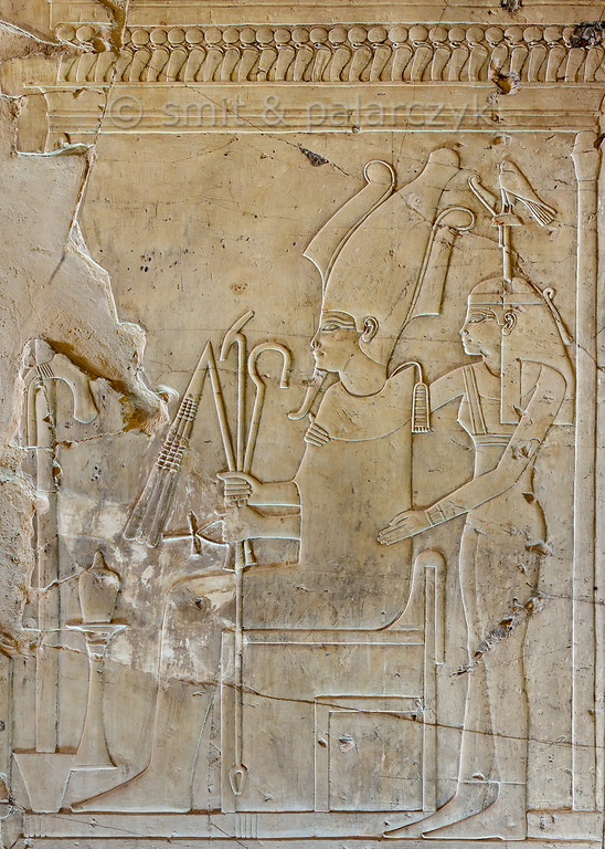 """[EGYPT 29332] Osiris and Hathor-Imentet in Khaemhat's tomb at Luxor.'  A well crafted relief in the tomb of Khaemhat shows a seated Osiris embraced from behind by the Goddess of the West (Hathor-Imentet). She is the mistress of the west, the land of the deceased, and wears the hieroglyph for 'west' as a headdress. Khaemhat (also known as Mahu) was an 18th dynasty royal scribe and 'Overseer of the Granaries of Upper and Lower Egypt. His tomb (TT 57) is located in the Sheikh Abd el Qurnah Necropolis on the Westbank at Luxor. It is one of the socalled """"Tombs of the Nobles"""" and dates to the reign of Amenhotep III. Photo Mick Palarczyk and Paul Smit."""