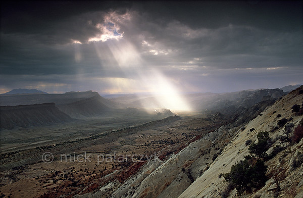 [USA.UTAH 28196] 'Thunderstorm over the Waterpocket Fold.'  	As a thunderstorm crosses Capitol Reef National Park, an isolated beam of light illuminates the Waterpocket Fold, a 65 million year old earthfold. The view is from Strike Overlook, looking south. Photo Mick Palarczyk.