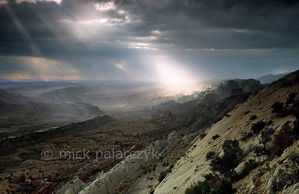 [USA.UTAH 28199] 'Thunderstorm over the Waterpocket Fold.'  As a thunderstorm crosses Capitol Reef National Park, an isolated beam of light illuminates the Waterpocket Fold, a 65 million year old earthfold. The view is from Strike Overlook, looking south. Photo Mick Palarczyk.