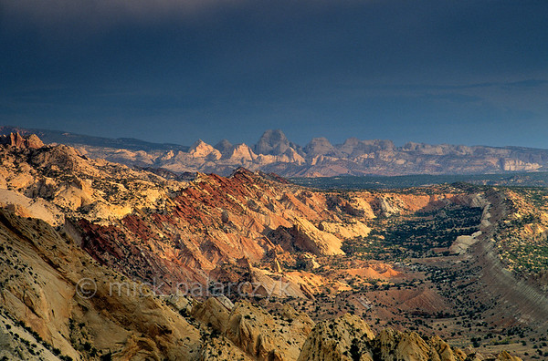 [USA.UTAH 28182] 'Waterpocket Fold seen from Strike Overlook.'  	In the Waterpocket Fold, a 65 million year old earthfold at Capitol Reef National Park, different rock-formations surface in straight lines. The geologic  layers, which were originally horizontal, were formed from sediments deposited over hundreds of millions of years in seas, tidal flats and deserts. As wind and water continue slowly to erode the fold, new features are created from the rock. The view is from Strike Overlook, looking north. Photo Mick Palarczyk.