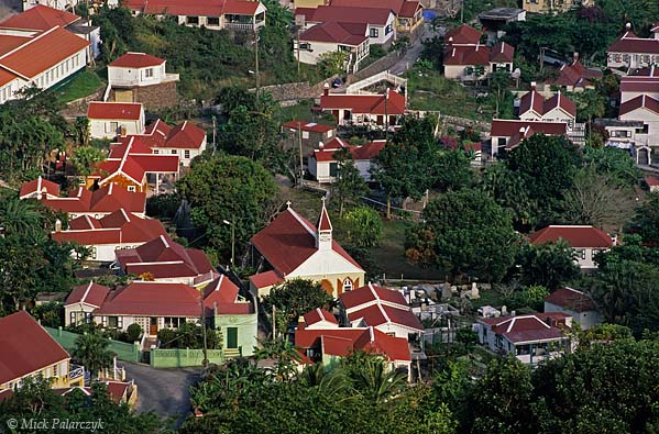 [ANTILLES.SABA 25.468] 'Red roofs.'	 Red roofed cottages of Windwardside surround the Anglican Holy Trinity Church, built in 1877. Photo Mick Palarczyk.