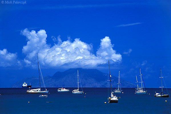 [ANTILLES.SABA 25.465] 'Mountain island.'  Its volcanic top shrouded in clouds, Saba rises above yachts moored near the coast of neighbouring island St. Eustatius. The island is situated 250 km east of Puerto Rico. Photo Mick Palarczyk.