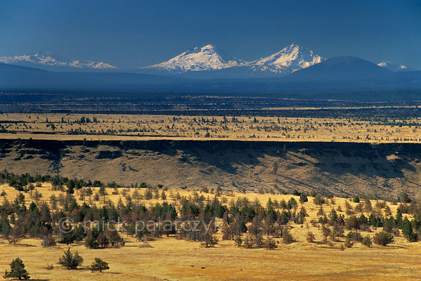 [USA.OREGON 28851] 'Prairie of Schoolie Flat.'  The prairie of Schoolie Flat is located in the center of the Warm Springs Indian Reservation. The yellow expanse of the flatland is bisected by the canyon of the Warm Springs River. On the horizon, the snowcapped Sisters, volcanos in the Cascades Mountain Range, can be seen. Photo Mick Palarczyk.