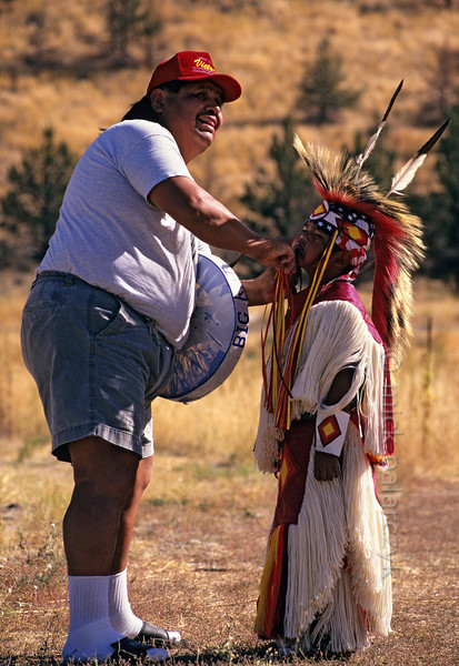 [USA.OREGON 28835] 'Indian father and son.'  A father prepares his son, a young member of the Walla Walla (or Warm Springs) Indian tribe, for a dance on the plains near Warm Springs town. Photo Mick Palarczyk.