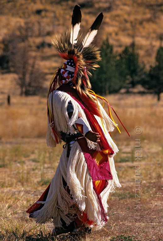 [USA.OREGON 28832] 'Indian boy.'  	A young member of the Walla Walla (or Warm Springs) Indian tribe, performing a dance on the plains near Warm Springs town. Photo Mick Palarczyk.