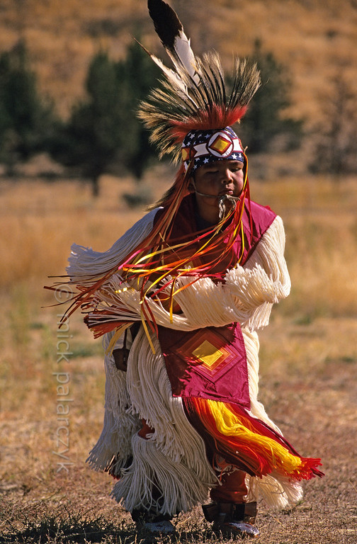 [USA.OREGON 28833] 'Indian boy.'  	A young member of the Walla Walla (or Warm Springs) Indian tribe, performing a dance on the plains near Warm Springs town. Photo Mick Palarczyk.