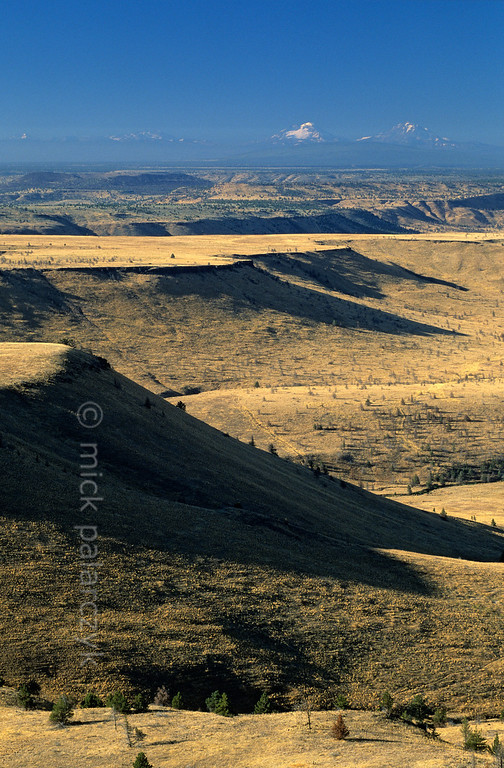 """[USA.OREGON 28826] 'Tablelands near Deschutes River.'  Tablelands near the canyon of the Deschutes River, seen from Tee Wees Butte, north of Warm Springs town. These lands are part of the Warm Springs Indian Reservation. On the horizon the snowcapped """"Sisters"""" are visible"""": three volcanos in the Cascades Mountain Range. Photo Mick Palarczyk."""