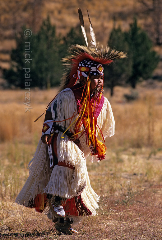 [USA.OREGON 28831] 'Indian boy.'  	A young member of the Walla Walla (or Warm Springs) Indian tribe, performing a dance on the plains near Warm Springs town. Photo Mick Palarczyk.