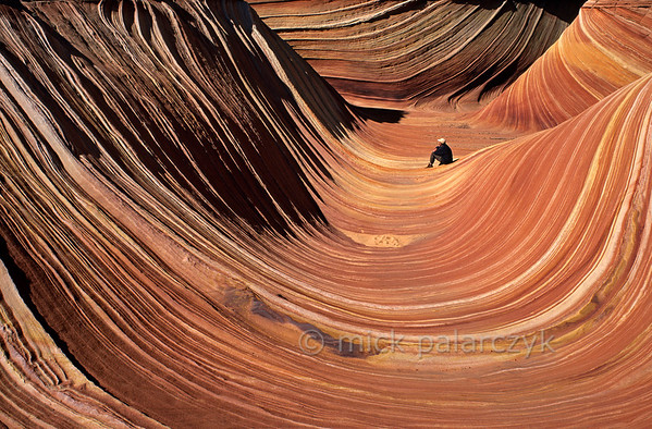 "[USA.ARIZONA 27994] 'Hiker in The Wave.'  	The hiker who enters ""The Wave"" in the Coyote Buttes nature reserve (part of the Vermilion Cliffs Wilderness) may think he is stepping into a sticky red fluid with white stripes, something like sour cream stirred into pumpkin soup. But this geological wonder actually consists of 200 million years old fossilized sand dunes. Photo Mick Palarczyk."