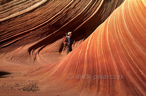 """[USA.ARIZONA 27997] 'Hiker in The Wave.'  The hiker who enters """"The Wave"""" in the Coyote Buttes nature reserve (part of the Vermilion Cliffs Wilderness) may think he is stepping into a sticky red fluid with white stripes, something like sour cream stirred into pumpkin soup. But this geological wonder actually consists of 200 million years old fossilized sand dunes. Photo Mick Palarczyk."""