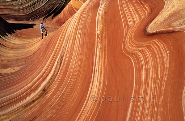 "[USA.ARIZONA 27991] 'Hiker in The Wave.'  	The hiker who enters ""The Wave"" in the Coyote Buttes nature reserve (part of the Vermilion Cliffs Wilderness) may think he is stepping into a sticky red fluid with white stripes, something like sour cream stirred into pumpkin soup. But this geological wonder actually consists of 200 million years old fossilized sand dunes. Photo Paul Smit."