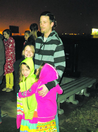 The Traxler girls, from left, Starr, Serenity and Sierra, snuggle up with dad Jason during the annual Sunrise Service at the Cross of the Crossroads in Effingham. Temperatures were in the mid 40 with a stiff north wind.