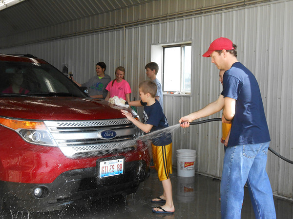 Students and volunteers wash cars at a fundraiser at Walk's Auto Body in Teutopolis. Teutopolis Sportsbackers booster club will use proceeds from the fundraiser to prevent cuts from Unit 50 athletic programs.