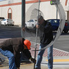 Todd Lohman, left, and Matt Wortman set up a new sculpture at the corner of Fifth Street and Jefferson Avenue.