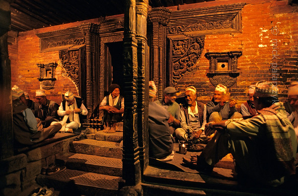 [NEPAL.KATHMANDUVALLEY 27490] 'Bhajan in Bhaktapur's Bhairava Temple.'  	On the eve Bhaktapur's New Year's festival (Bisket) men have gathered in the entrance gallery of the Bhairava Temple in Taumadhi Square for evening bhajan (hymn-singing). Photo Mick Palarczyk.