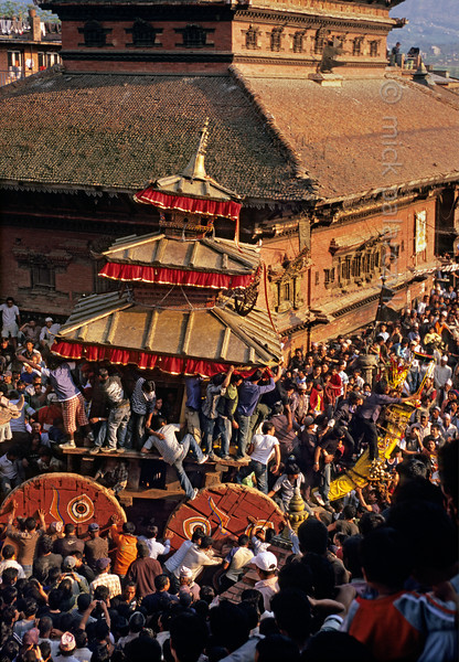 [NEPAL.KATHMANDUVALLEY 27455] 'Bisket festival in Bhaktapur's Taumadhi Square.'  Bhaktapur's New Year's festival (Bisket) starts with a tug-of-war in Taumadhi Square, in which residents of the upper and lower halves of the city try to pull a chariot to their respective sides. The enormous temple shaped rath (vehicle of the gods) contains a mask of the god Bhairava, which is normally kept in the Bhairava Temple that is visible behind the chariot. Photo Mick Palarczyk.