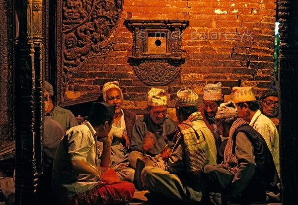 [NEPAL.KATHMANDUVALLEY 27487] 'Bhajan in Bhaktapur's Bhairava Temple.'  	On the eve Bhaktapur's New Year's festival (Bisket) men have gathered in the entrance gallery of the Bhairava Temple in Taumadhi Square for evening bhajan (hymn-singing) to the accompaniment of cymbels. Photo Mick Palarczyk.