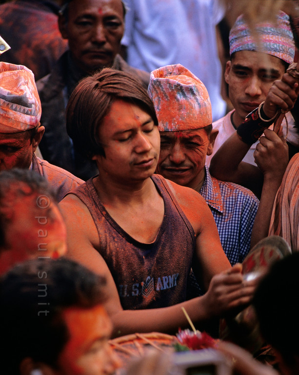 [NEPAL.KATHMANDUVALLEY 27511] 'Man with cymbals in Thimi.'  On the second day of the Nepalese New Year the narrow lanes of Thimi are crowded with 32 teams of men from each town quarter carrying a khat - a ceremonial palanquin occupied by deities. Each team is accompanied by its own musicians, covered in brilliant orange-red powder. For to drown one's fellows in vermilion powder is a token of respect, just as it honours the gods and goddesses. Photo Paul Smit.