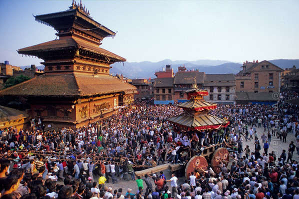 [NEPAL.KATHMANDUVALLEY 27450] 'Tug-of war in Bhaktapur.'  	Bhaktapur's New Year's festival (Bisket) starts with a tug-of-war in Taumadhi Square, in which residents of the upper and lower halves of the city try to pull a chariot to their respective sides. The enormous temple shaped rath (vehicle of the gods) contains a mask of the god Bhairava, which is normally kept in the Bhairava Temple that is visible on the left. Photo Mick Palarczyk.
