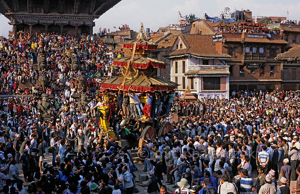 [NEPAL.KATHMANDUVALLEY 27454] 'Bisket festival in Bhaktapur's Taumadhi Square.'  	Bhaktapur's New Year's festival (Bisket) starts with a tug-of-war in Taumadhi Square, in which residents of the upper and lower halves of the city try to pull a chariot to their respective sides. The enormous temple shaped rath (vehicle of the gods) contains a mask of the god Bhairava. Photo Mick Palarczyk.
