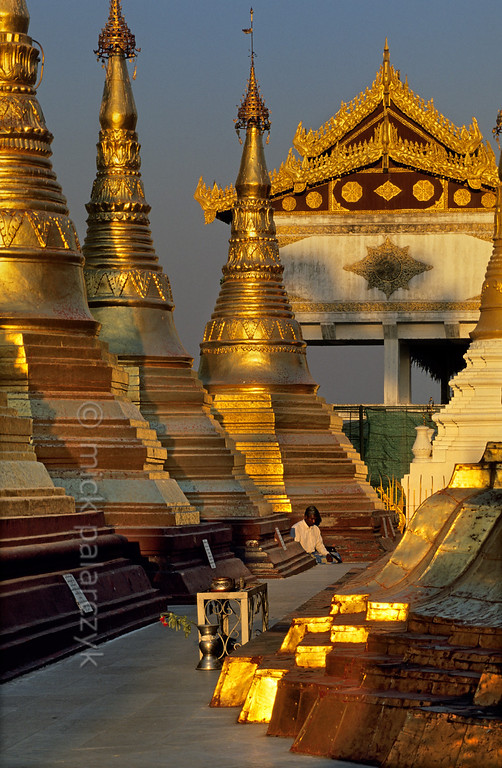 [BURMA 24.698] 'Golden meditation.'  	The terrace around the Naungdawyi Stupa in the northeastern corner of Yangon's Shwedagon temple is open only to meditating men. Photo Mick Palarczyk.
