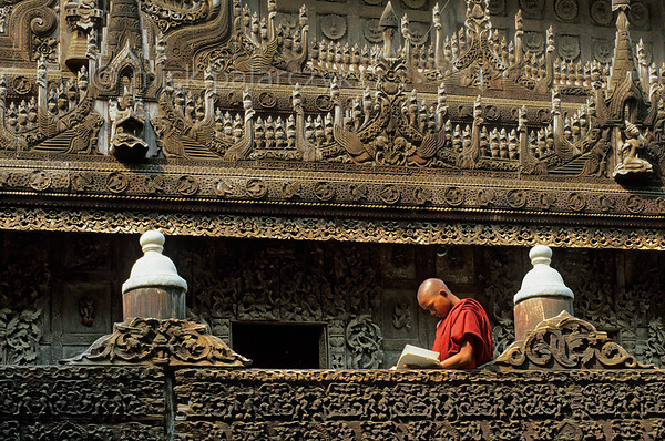 [BURMA 25.098] 'Studying monk.'  	Amid precious woodcarvings a young monk is studying on the elevated platform surrounding the Mandalay Shwenandaw Monastery. Photo Mick Palarczyk.