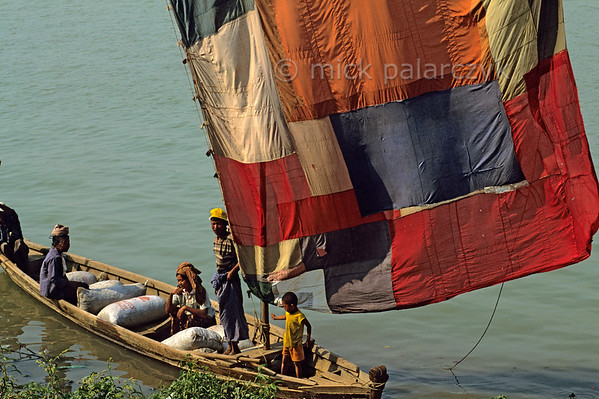 [BURMA 24.979] 'Sailing on the Chindwinn River.'  At Monywa, a boat on the Chindwinn River carries a sail which has been sewn together from different pieces of colourful cloth. The Chindwinn is a tributary of the Irrawaddy. Photo Mick Palarczyk.