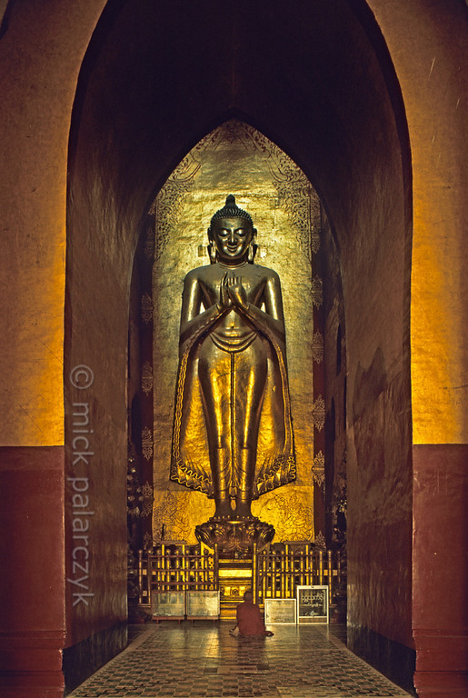 [BURMA 24.893] 'Buddha in the Ananda Temple.'  	At Bagan this 9.5 m. standing Buddha decorates the southern niche in the central cube of the early 12th century Ananda Temple. Photo Mick Palarczyk.