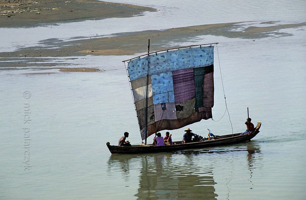 [BURMA 24.982] 'Butterfly boat.'  	Many sailing boats in Burma, as here on the Chindwinn at Monywa, have the looks of a colourful butterfly as their sails are made up of different pieces of cloth. The Chindwinn is a tributary of the Irrawaddy. Photo Mick Palarczyk.