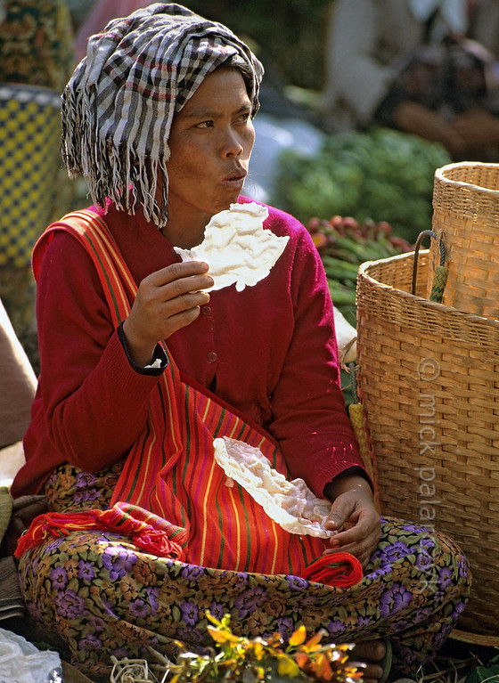 [BURMA 24.781] 'Eating waffles.'  	Waiting for her next customer, a women eats paper-thin waffles on the market of Kalaw. Photo Mick Palarczyk.