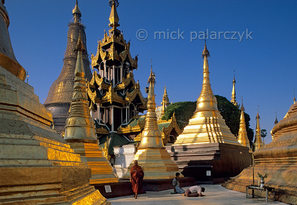 [BURMA 24.674] 'Worshipping at the Shwedagon Pagoda.'  	Worshippers bow at the foot (right) of the Naungdawyi Stupa in the northeastern corner of Yangon's Shwedagon Temple. In the background towers the central stupa of the temple complex. Photo Mick Palarczyk.