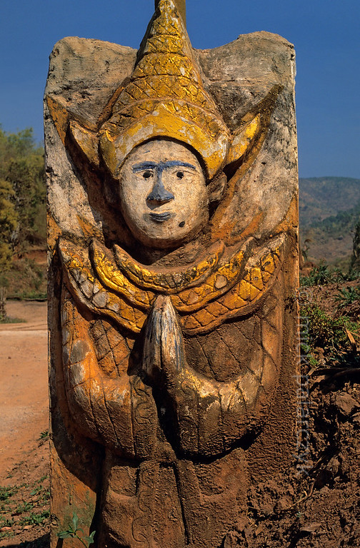 [BURMA 24.776] 'Monastic invitation.'  	A sculpted stone, representing a nat (protective spirit), flanks the entrance way to a monastery in the highlands west of Kalaw. Photo Mick Palarczyk.