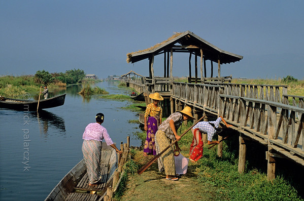 [BURMA 24.801] 'Stilted walkway.'  	A stilted walkway connects the lake-based village of Maing Thauk (visible in the distance) to the eastern shore of the Inle Lake. A group of villagers, having just arrived in a boat, store their oars under the walkway. Photo Mick Palarczyk.