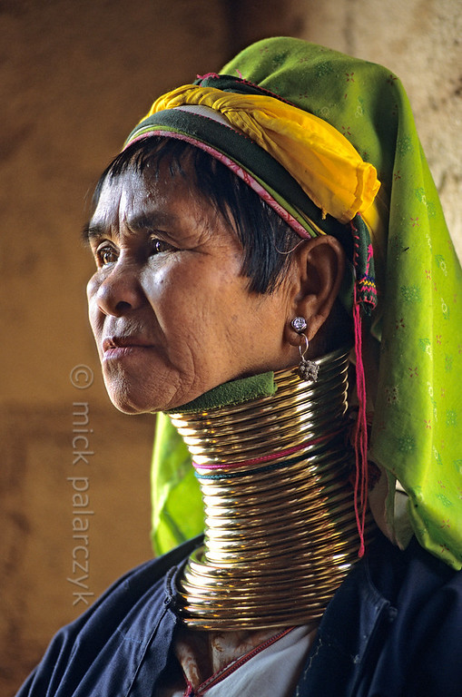"[BURMA 24.855] 'Doni, a giraffe woman.'  	Doni, a member of the Padaung tribe, also known as the tribe of the ""giraffe women"", lives in Indein, a village on the west shore of the Inle Lake. The effect of the long neck is attained by the heavy rings pushing down the collar-bone and ribs. Photo Mick Palarczyk."