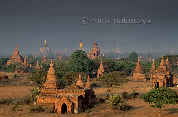 [BURMA 24.880] 'Bagan plain seen from Bulethi Stupa.'  The Bagan plain houses some two thousand temples and stupas. They are the 11th-13th century remnants of the now vanished royal city of Bagan. Here the plain is seen in the early morning from the Bulethi Stupa, looking west, with on the horizon the Thatbyinnyu Temple (left, with small golden spire) and the Ananda Temple (with big golden spire). Photo Mick Palarczyk.