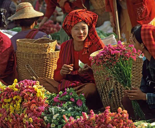 [BURMA 24.780] 'Selling flowers.'  	Highland woman selling flowers on the market of Kalaw. Photo Mick Palarczyk.