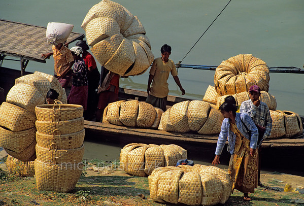 [BURMA 24.981] 'Unloading baskets.'  On the bank of Chindwinn River in Monywa, villagers are unloading home made baskets from a barge to sell them on the market. The Chindwinn is a tributary of the Irrawaddy. Photo Mick Palarczyk.