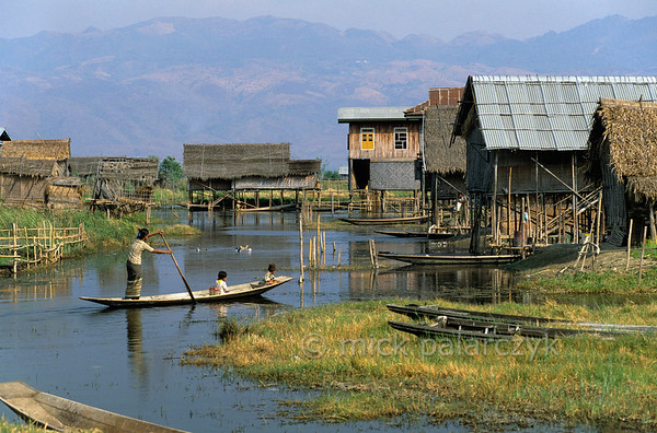 [BURMA 24.813] 'The end of a school day.'  	At the end of a school day, Inle Lake villagers take their children home by boat to their stilted houses in Kaungdaing, on the northwestern shore of the lake. Photo Mick Palarczyk.