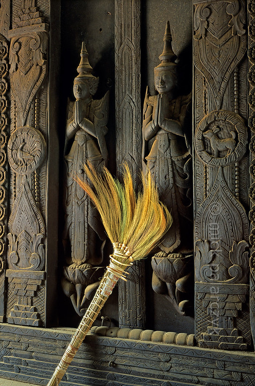[BURMA 25.106] 'Shwe In Bin Monastery.'  	A monk has left his broom against a pair of artfully carved doors at the Shwe In Bin Monastery in Mandalay. Photo Mick Palarczyk.