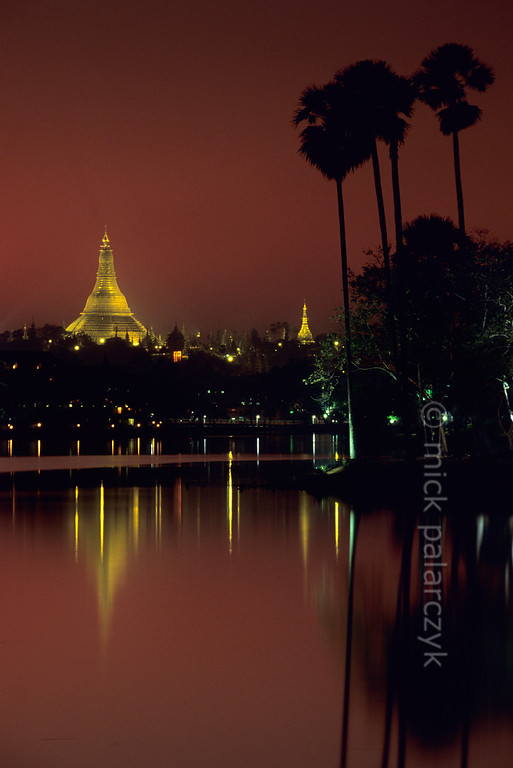 [BURMA 24.673] 'Kandawgyi Lake and Shwedagon Pagoda.'  	In the last glow of the evening the golden stupa of the Shwedagon Pagoda hovers above the mirror-like surface of Yangon's Kandawgyi Lake. Photo Mick Palarczyk.