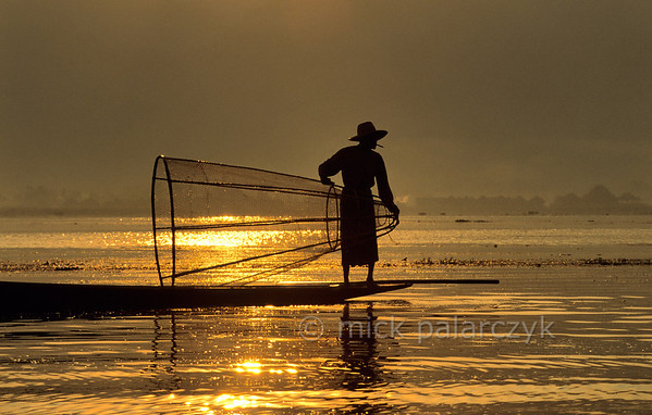 [BURMA 24.833] 'Searching for fish.'  	While the first sun-rays are piercing the haze over the Inle Lake, an Intha fisherman searches the lake for a catch. Photo Mick Palarczyk.