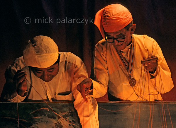 [BURMA 25.079] 'Playing marionettes.'  	In the Garden Villa Theatre at Mandalay an old puppet master and his pupil are manipulating their marionettes. Photo Mick Palarczyk.